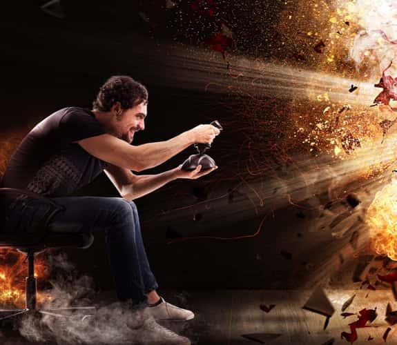Gamer alla console con joy pad circondato da un'effetto di esplosione
