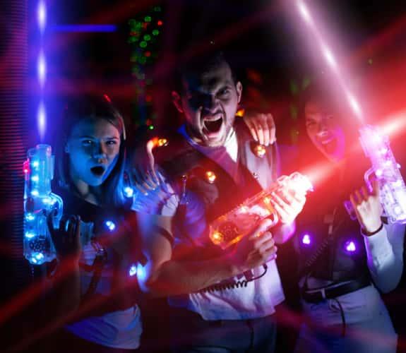 Ritratto di gruppo di giovani con fasci colorati di pistole laser
