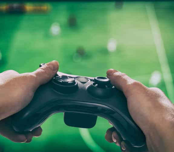 Controller nelle mani di un giocatore con schermo sullo sfondo