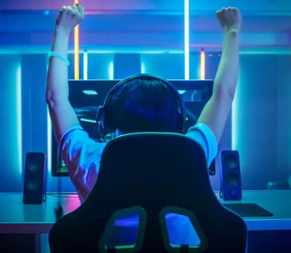 Ragazzo esultante di spalle mentre gioca a un video game in una stanza con vari neon blu