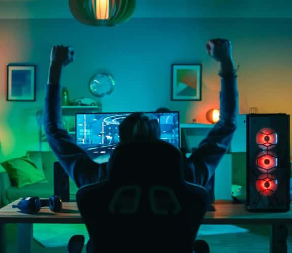 Ragazzo esultante di spalle mentre gioca a un video game in una stanza illuminata con vari colori